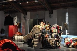 At Prato's Museo del Tessuto, piles of old clothes are arranged to simulate the atmosphere inside a textile factory where 'pickers' sort old clothes into categories so that the fabrics may be reused in current fashion.