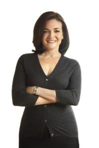 I'm not sure why this photograph was taken of Sheryl Sandberg. Looking her up and down, after the smile, her body language might look at ease, but it also looks a bit protective. And the gray cardigan may communicate that she's willing to listen, but the way she wears it says that you better make it quick.