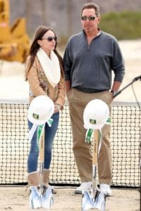 Larry Ellison, standing beside his well-tended to girlfriend, looks like he ought to find clothes that flatter him better, both in fit and in color.