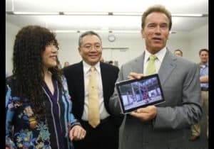 Calif. Gov. Arnold Schwarzenegger holds a tablet with a chip inside made by Marvell Seminconductor, as co-founder Weili Dai, left, and co-founder and CEO Sehat Sutardja, center, look on.