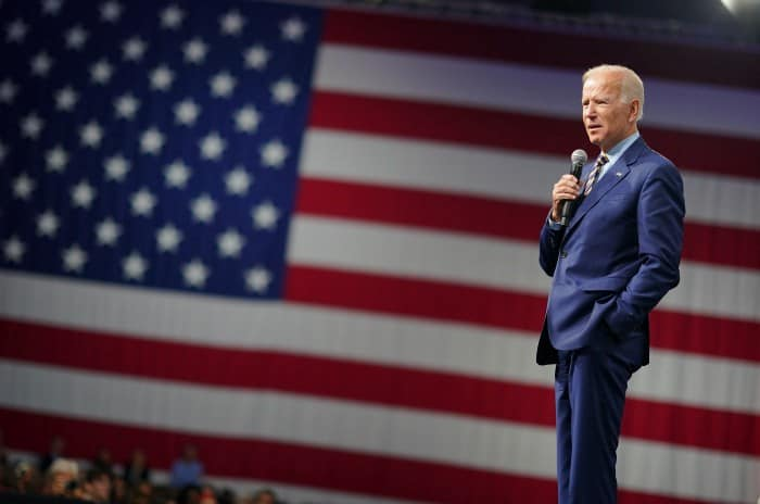 Joe Biden giving a speech with an American flag in the background